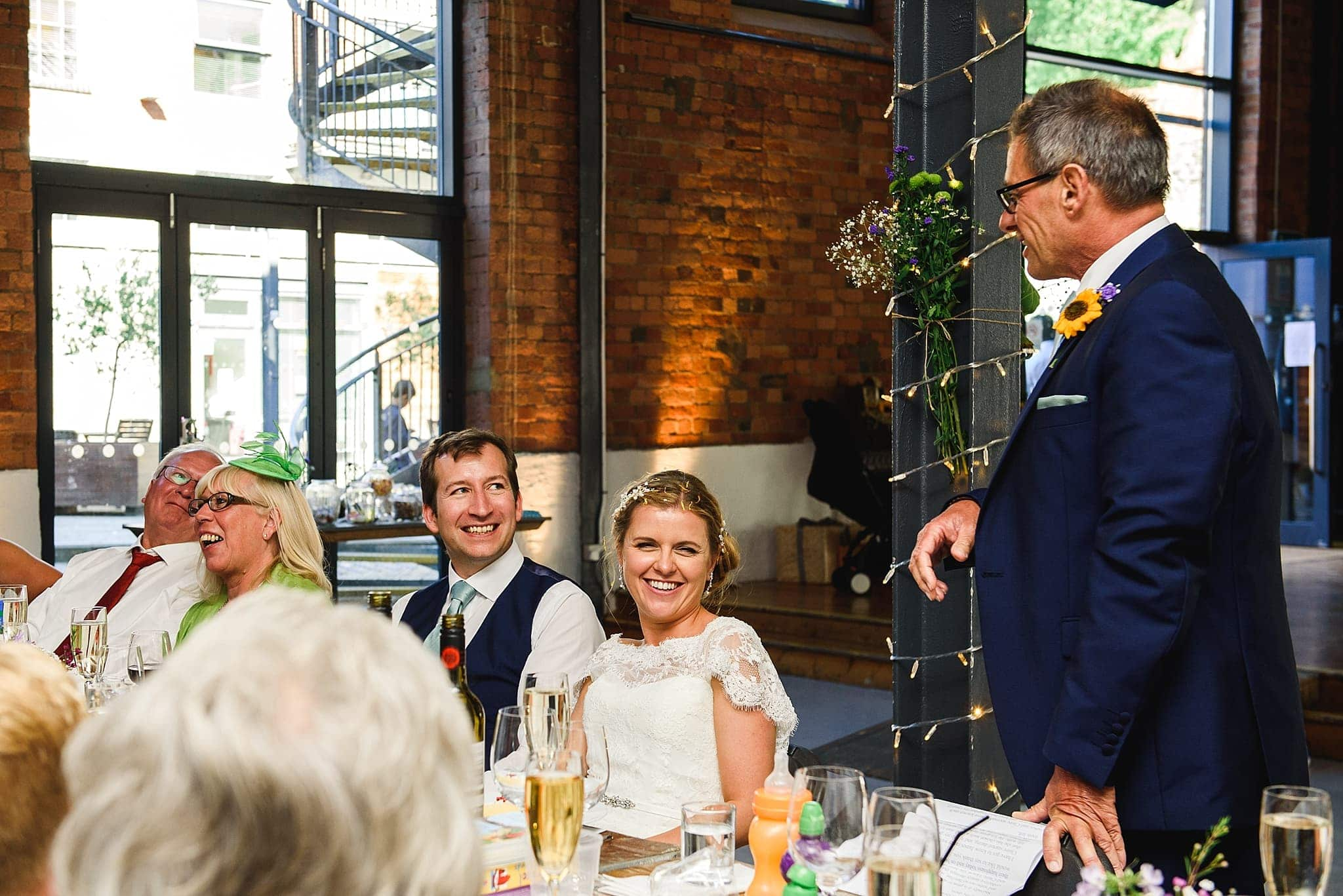 Father of the bride reads out his speech to his daughter and new husband on their wedding day at the paintwork's