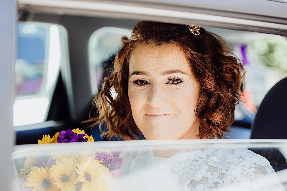 Bride looking out of her car window as she arrives at the Beachlands hotel for her wedding