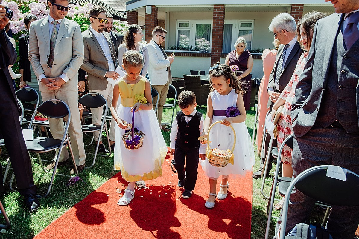 two flower girls with page boy sprinkling petals on red carpet of an outdoor wedding ceremony at the Beachlands hotel WSM