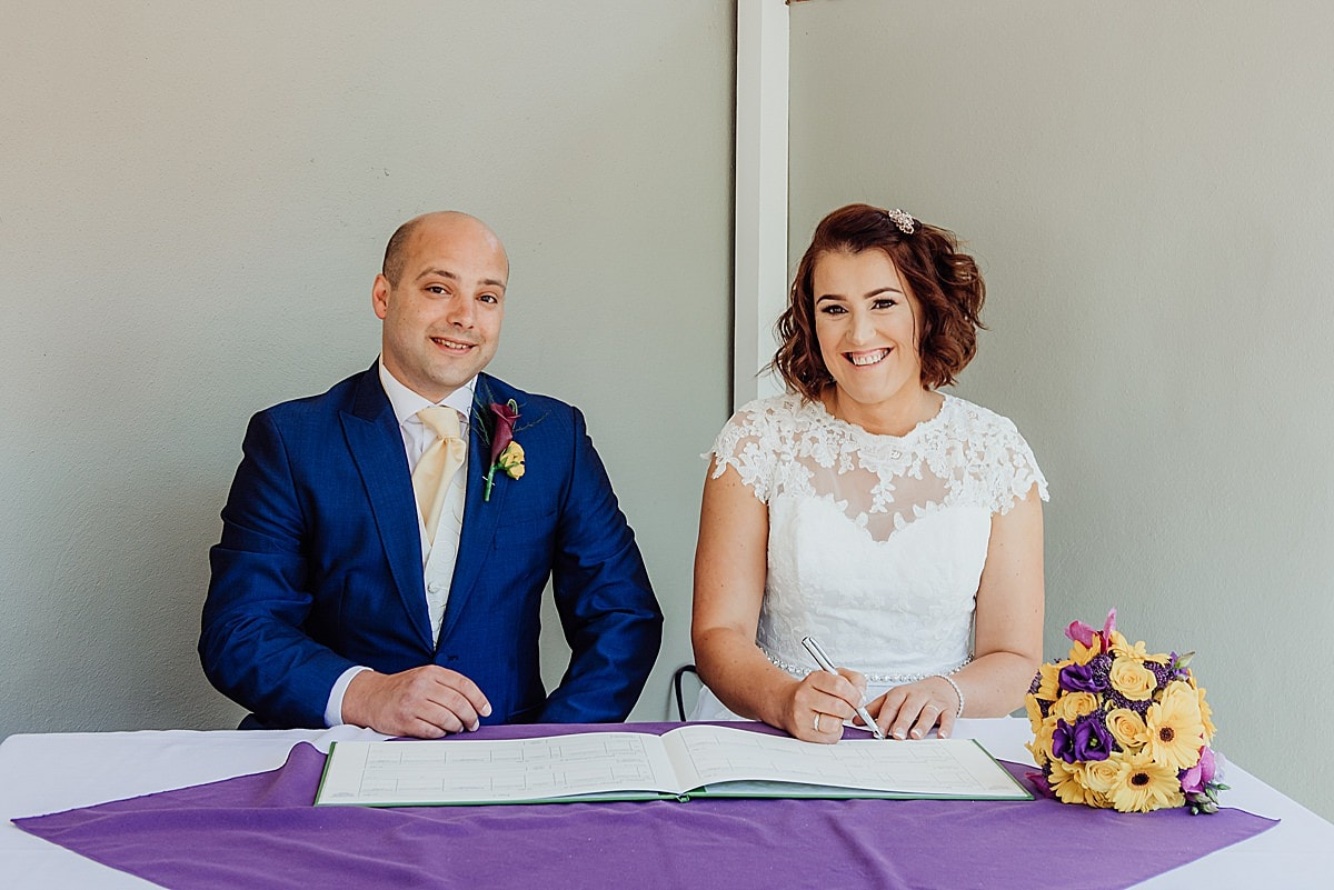 Newly married bride and groom signing the register at their wedding at the Beachlands hotel in Weston Super mare