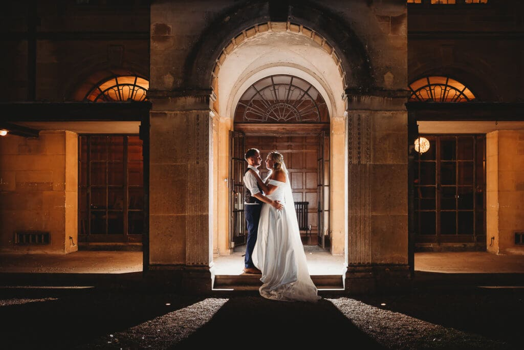 Bride and groom stand in archway of Coombe lodge at night back lit