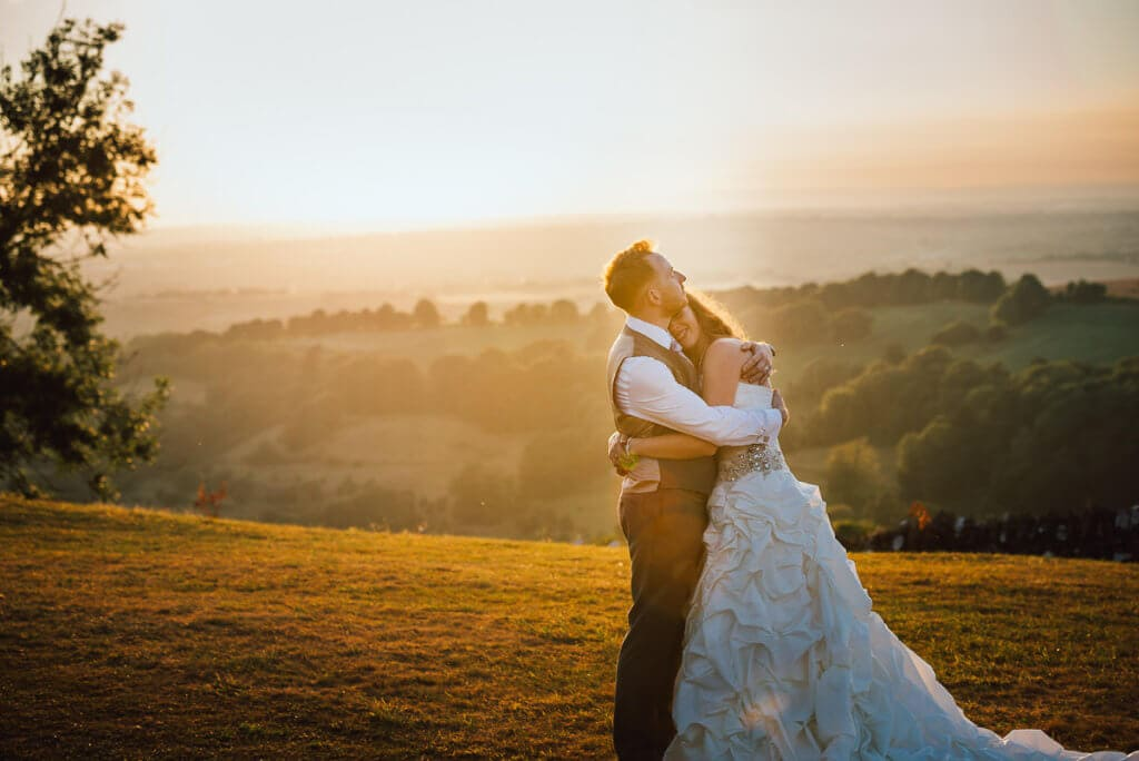 Bride and groom hug as the sun goes down over looking Bath country side