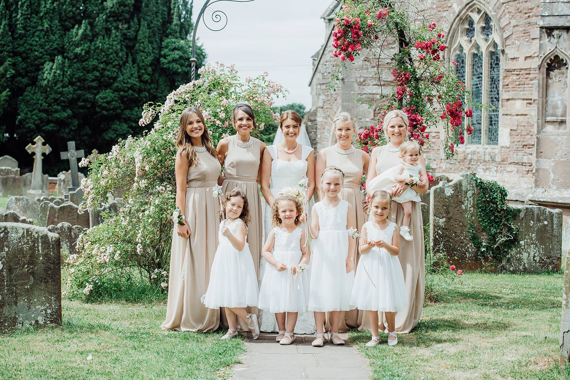 Bridesmaids stood posing in the grounds of St Michael's church Winterbourne Bristol