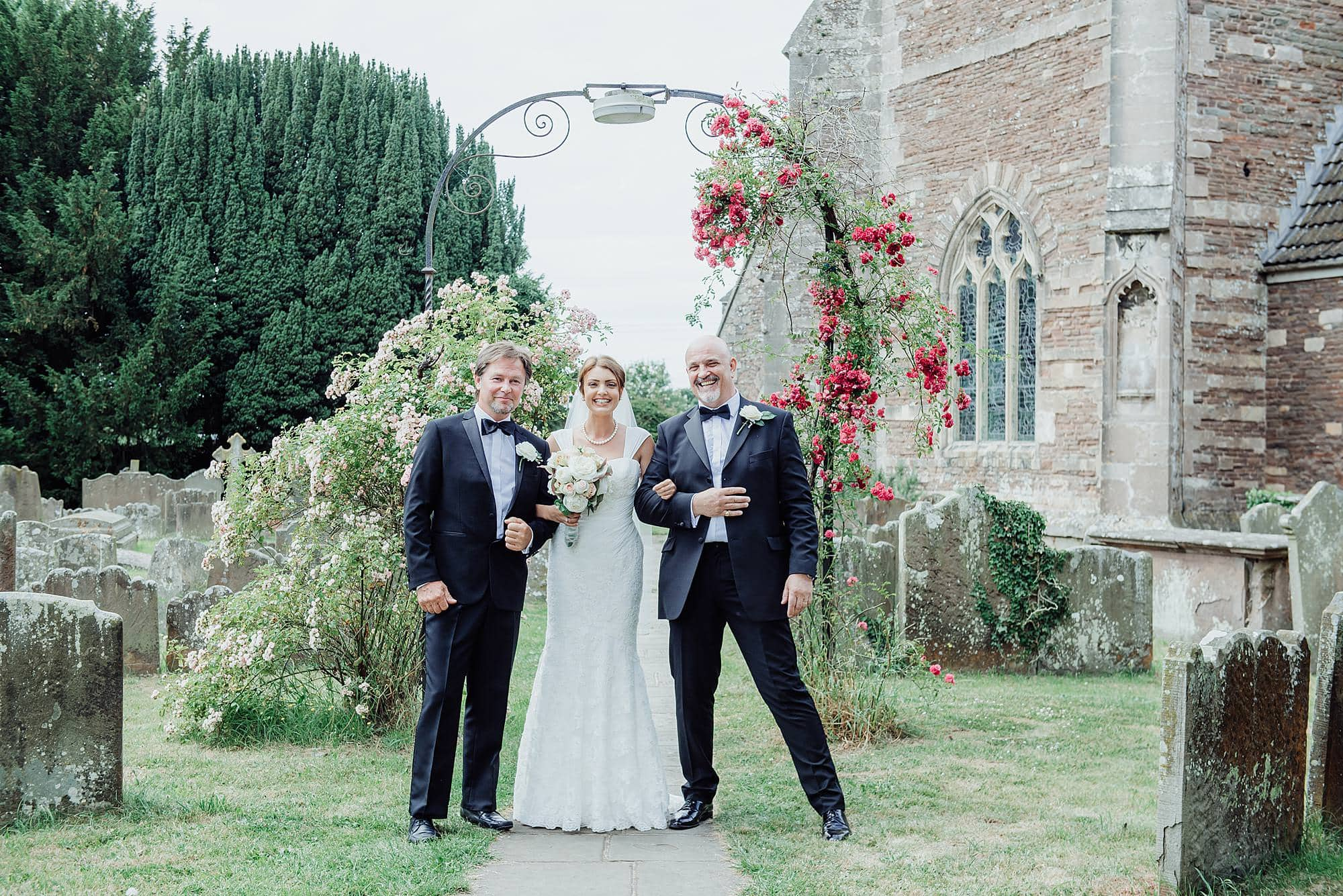 Bride stood with her two fathers outside of St Michael's church Winterbourne