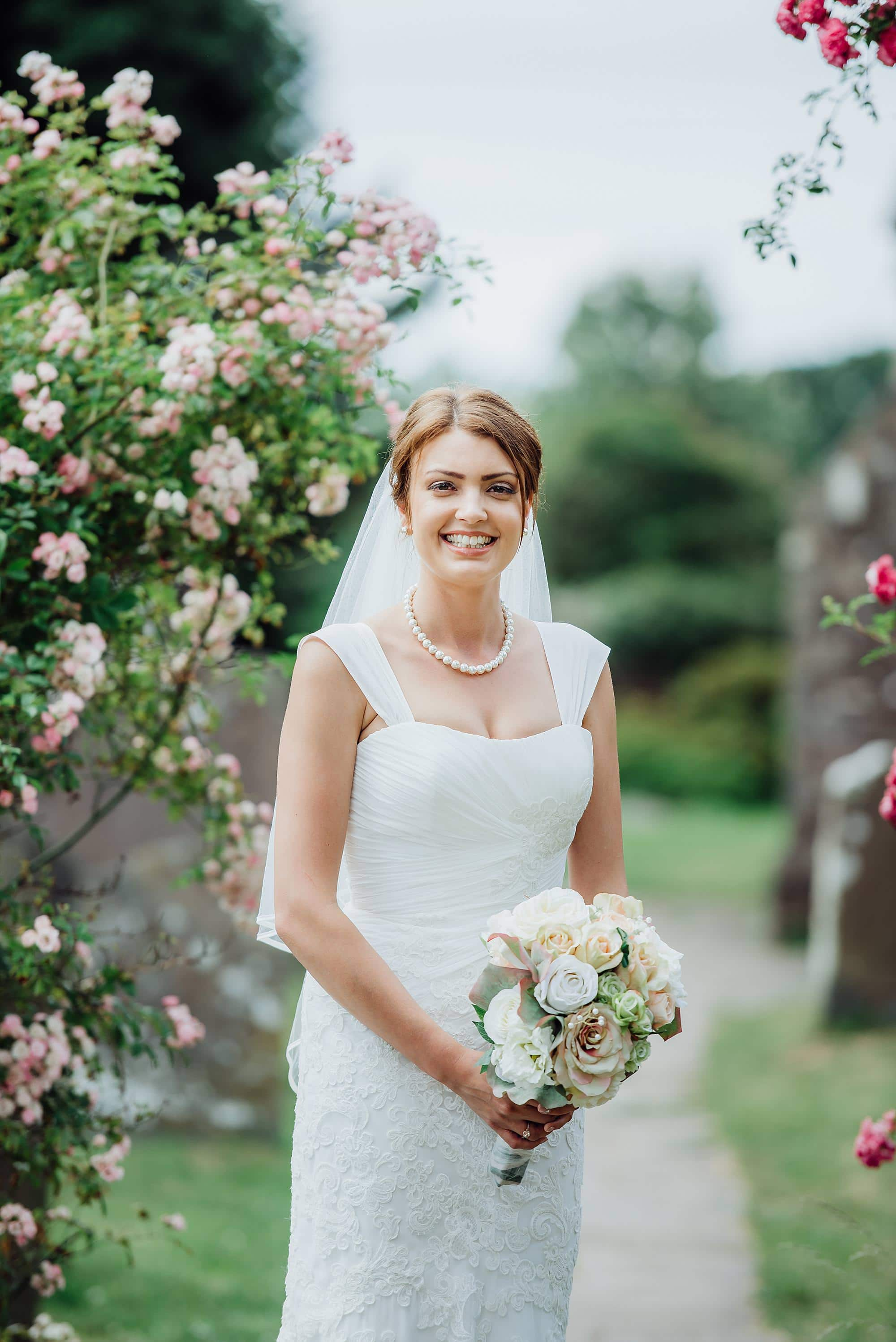 Bride stood in the garden of St Michael's church Winterbourne with beautiful flowers in the background