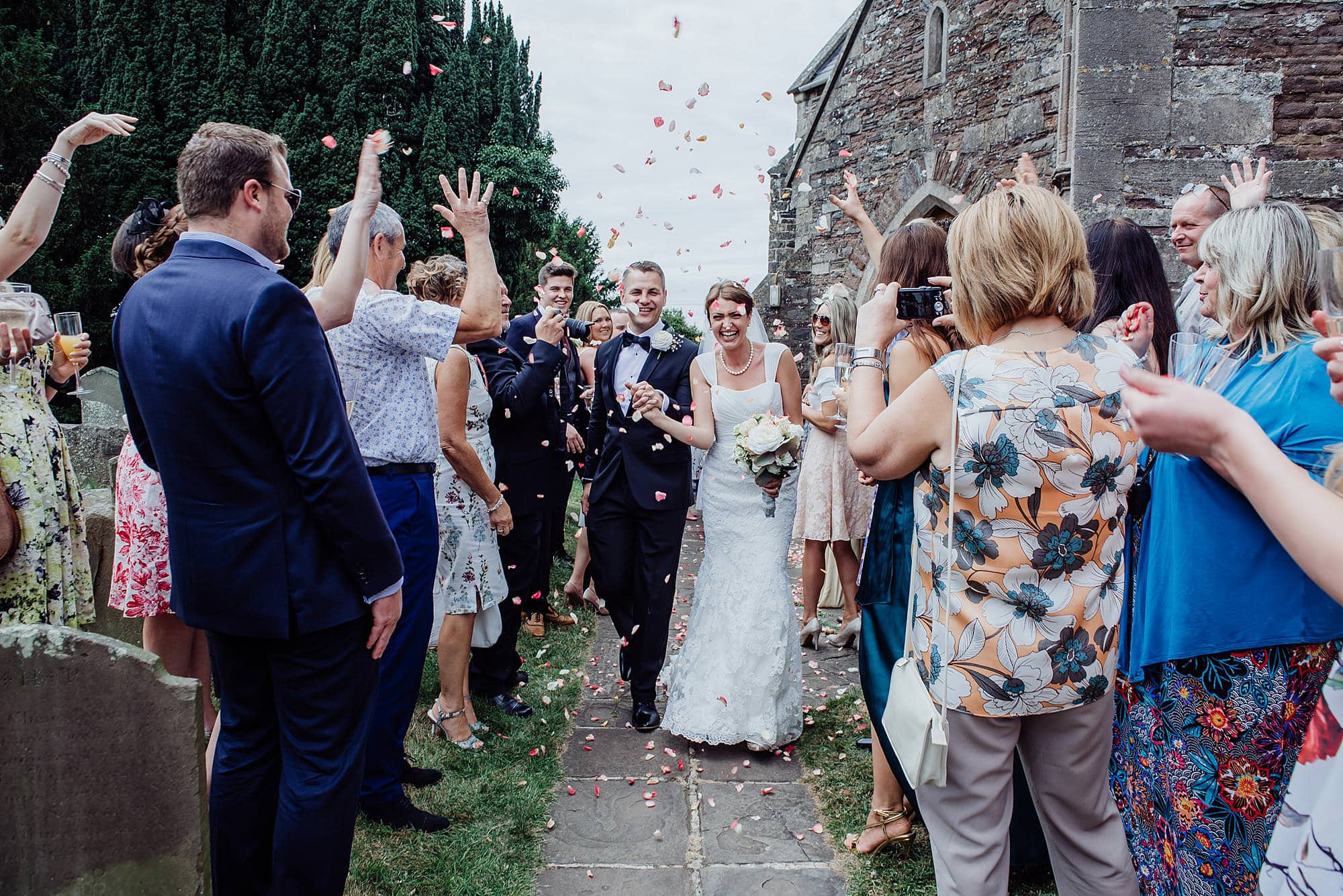 guests throwing confetti as bride and groom walk past them in the grounds of St Michael's church Winterborne