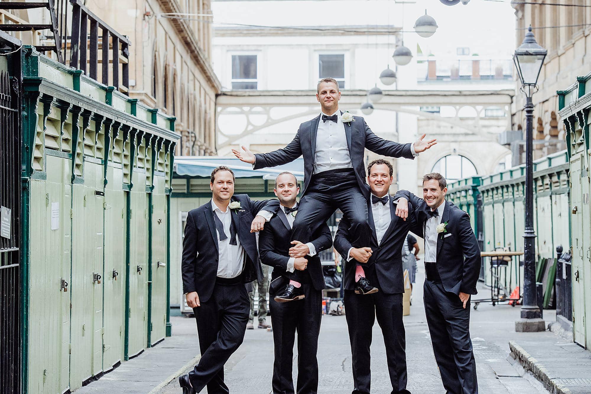 Groom sitting on the shoulders of his groomsmen outside the Rummer Hotel Bristol