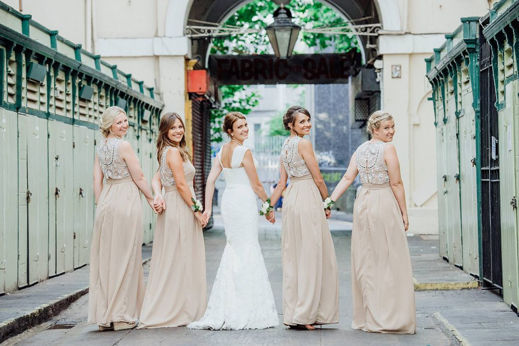 Bridesmaids walking hand in hand looking back towards the camera in St Nicks Market outside the Rummer hotel wedding