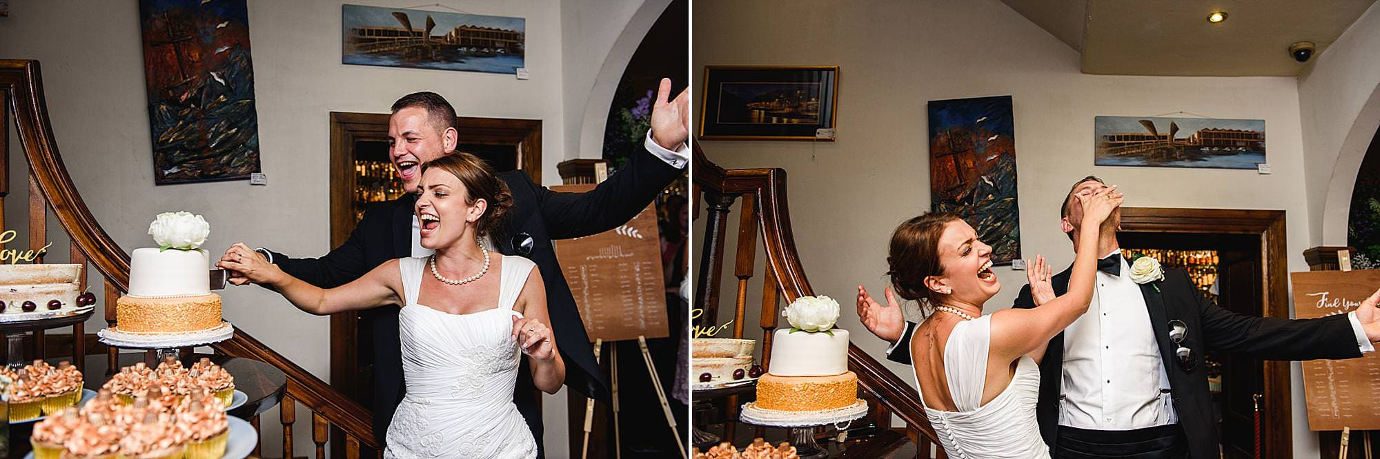 Bride and groom cut the cake and bride feeds groom at their Tummer hotel wedding Bristol