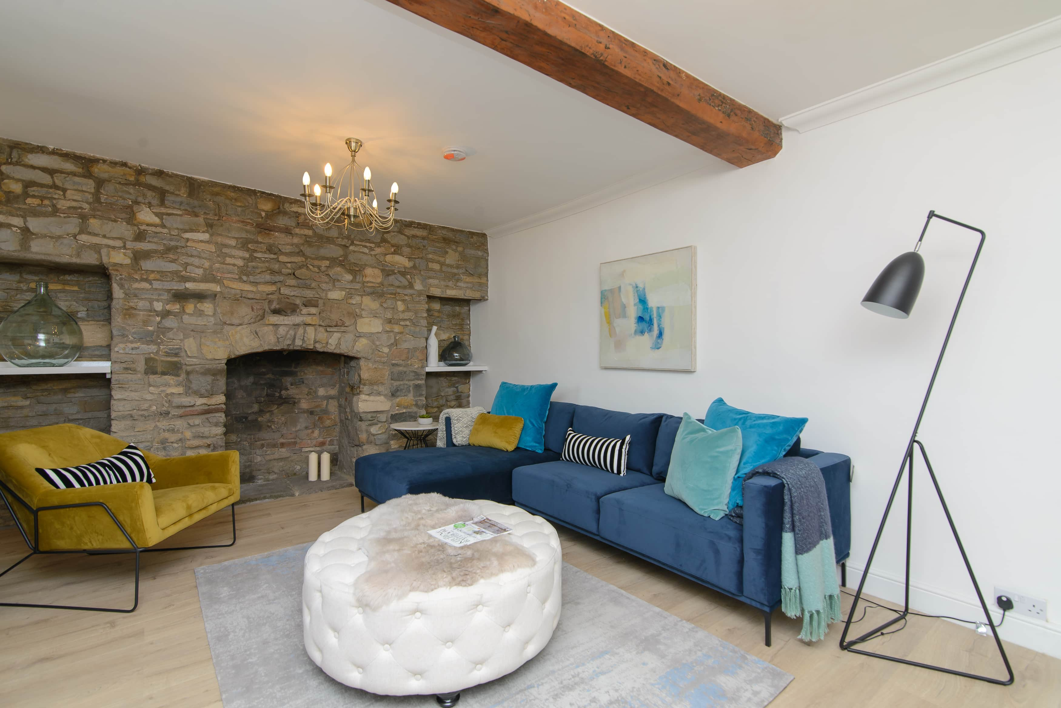 A stone wall living room cottage with blue designer sofa and yellow