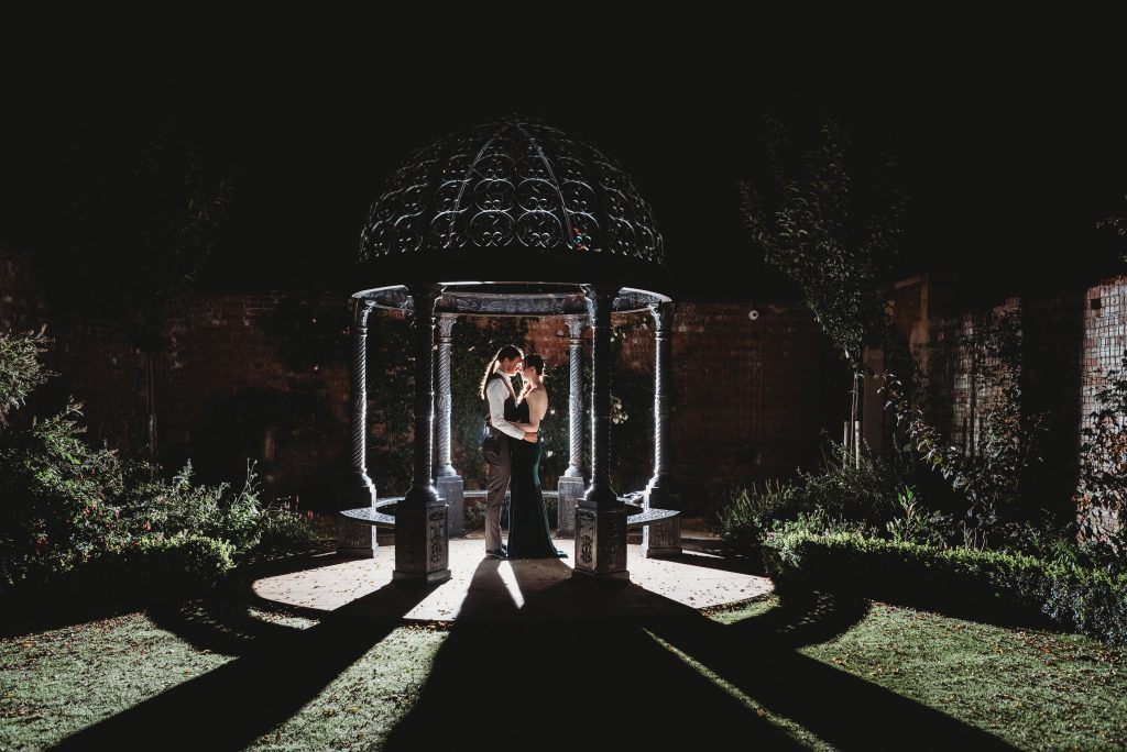 Night portrait of couple being back lit in the ground of Kings Weston House