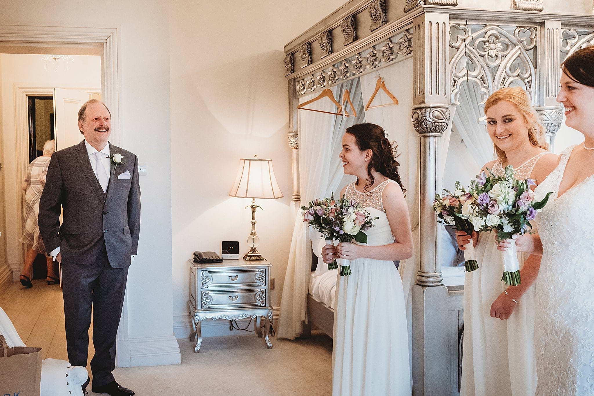 Father of the brides happy reaction as he walks into see his daughter on her wedding day in the bridal suit of Manor by the lake