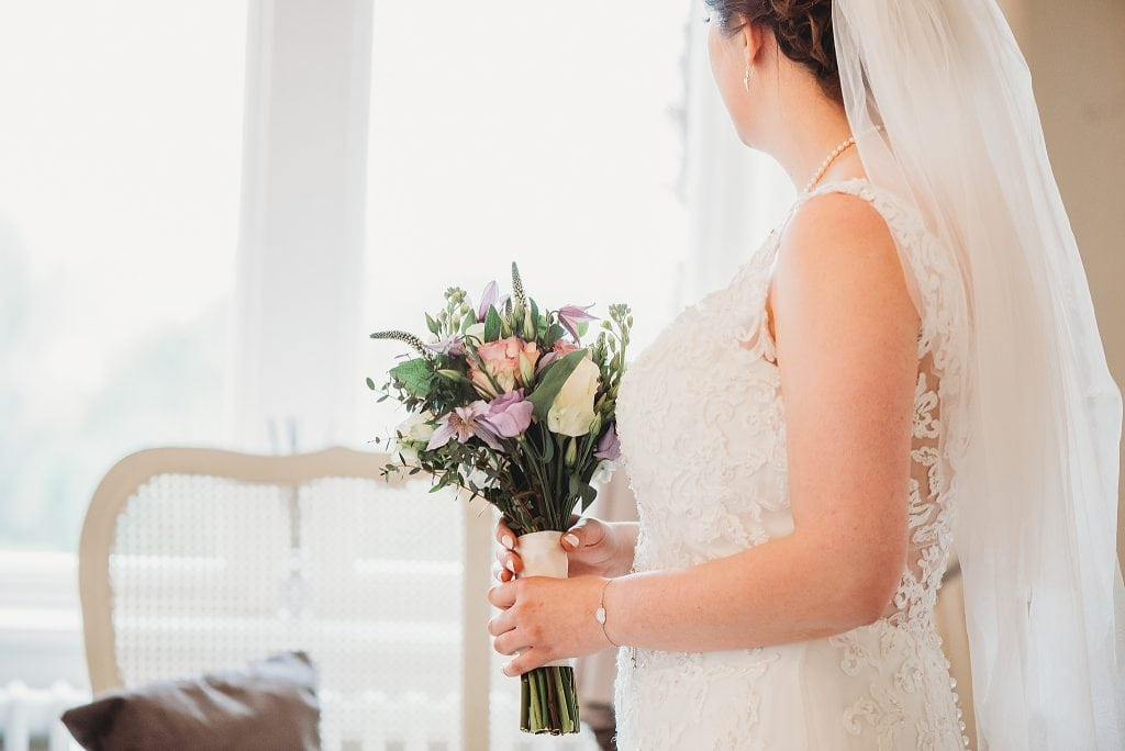 bride holding her bouquet of flowers looking out of the window in the bridal suite at Manor by the lake wedding venue