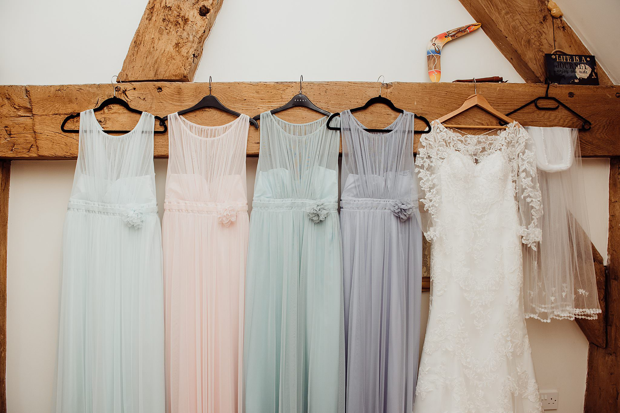 Wedding dress and multi coloured bridesmaids dresses hanging on a wooden beam