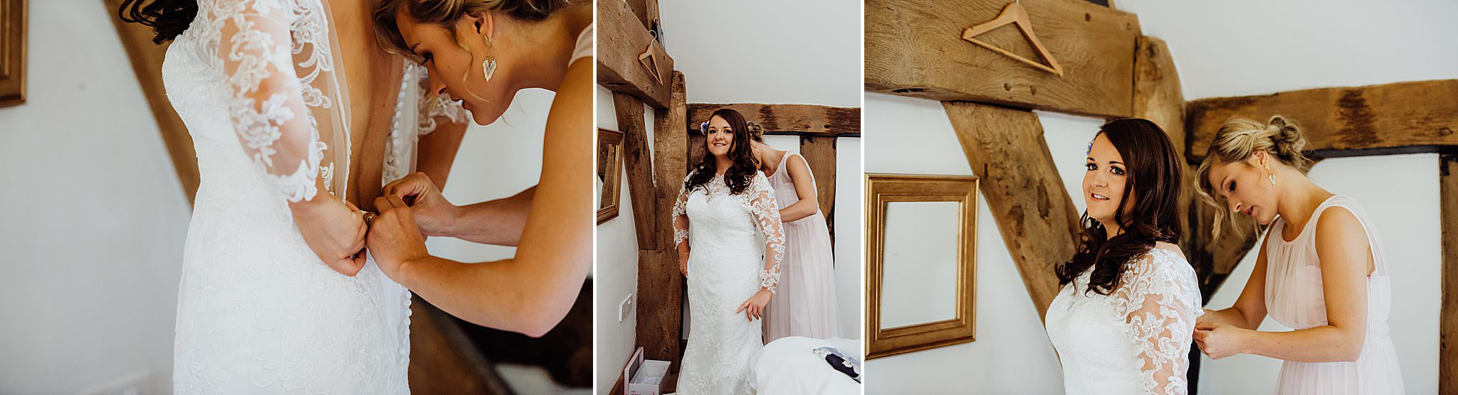 Bride putting on her wedding dress being helped by a bridesmaid