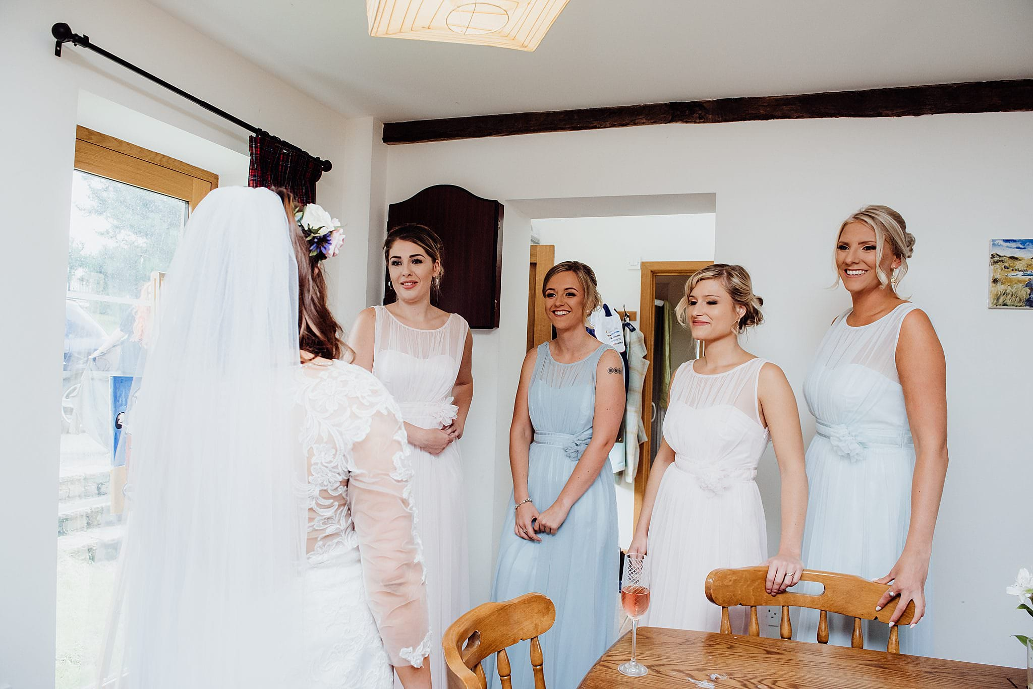 Bridesmaids stood in a line as they see the bride for the first time in her wedding dress