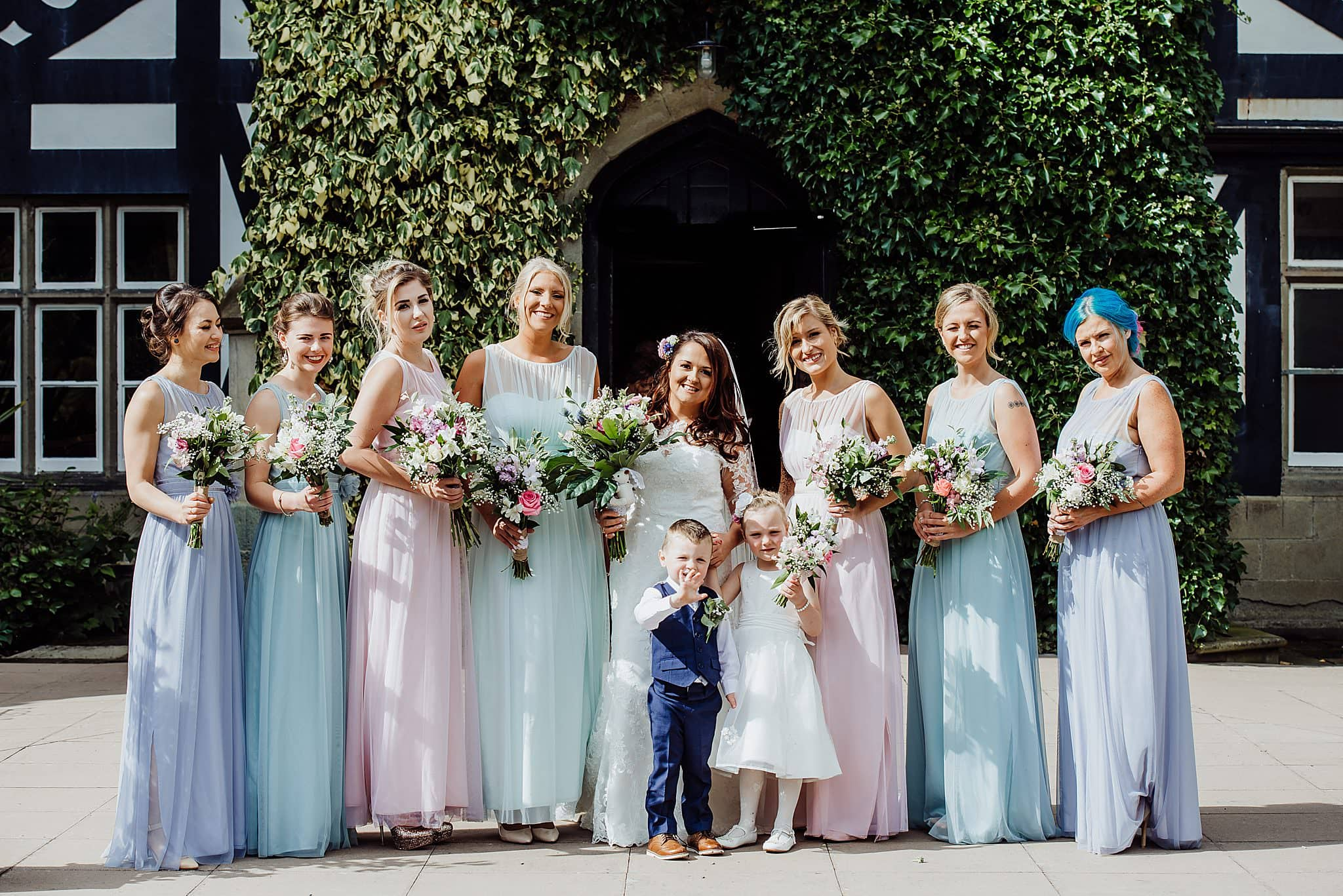 A large group photo of the wedding party with bridesmaids wearing multi coloured dresses