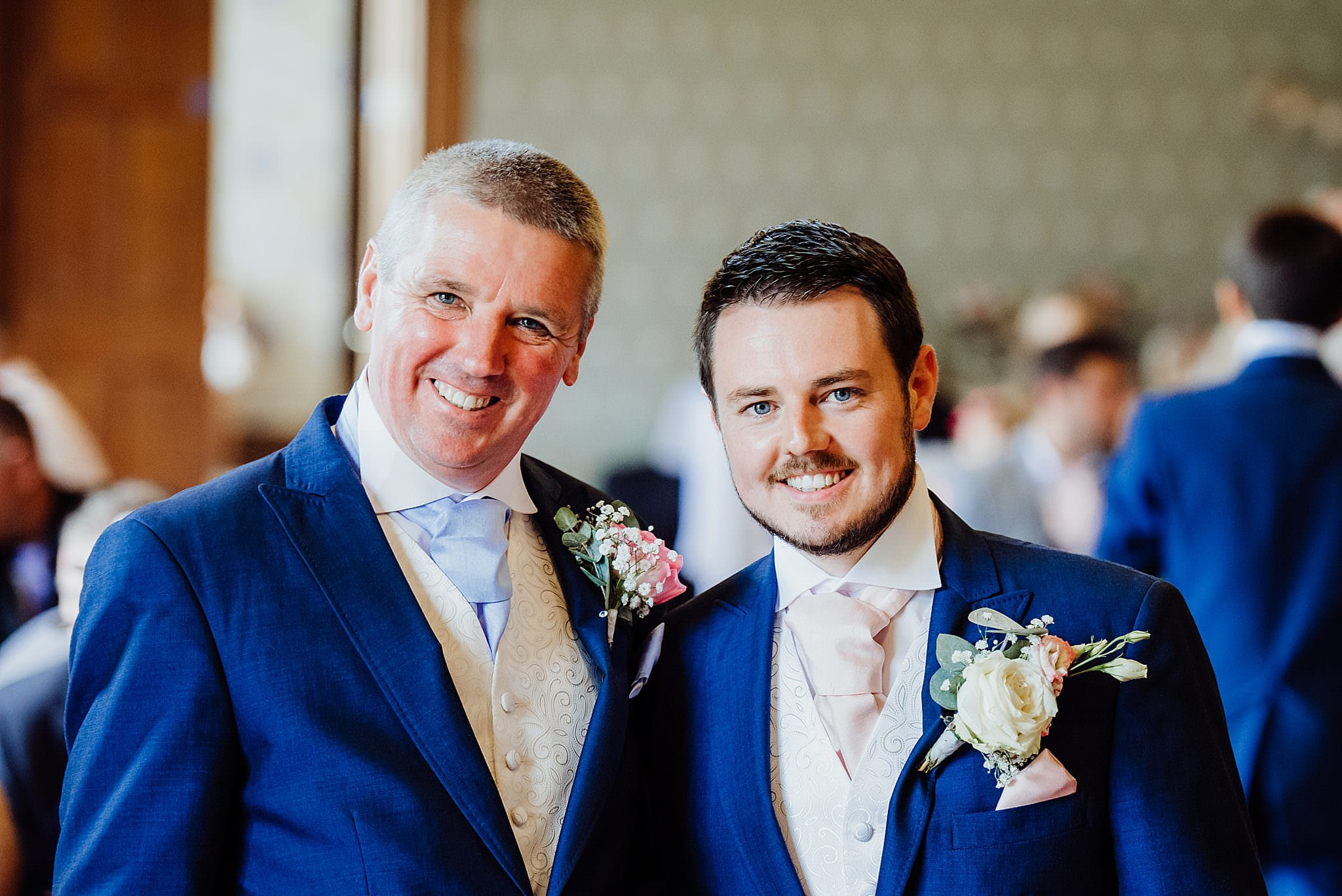 A smiling groom and his best man at a wedding ceremony at Gregnog Hall