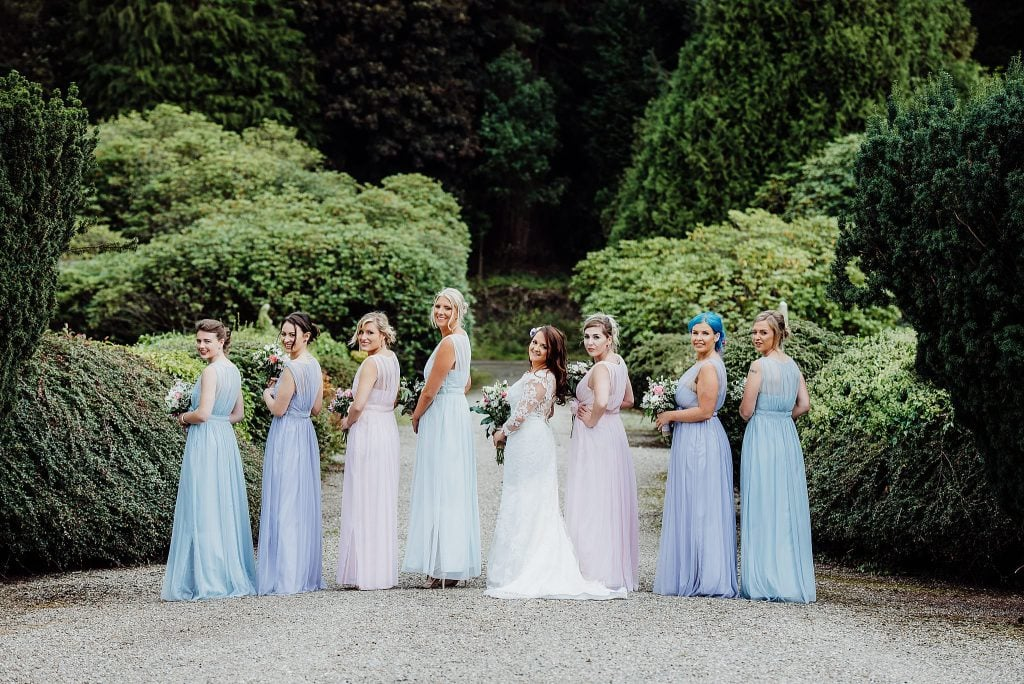 Bride with bridesmaids standing in a line looking back at the camera wearing multi coloured bridesmaids dress at Gregnog Hall wedding venue