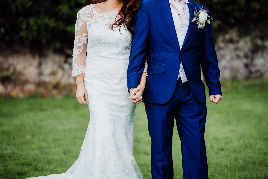 Close up photo of a bride and groom holding hands in the garden