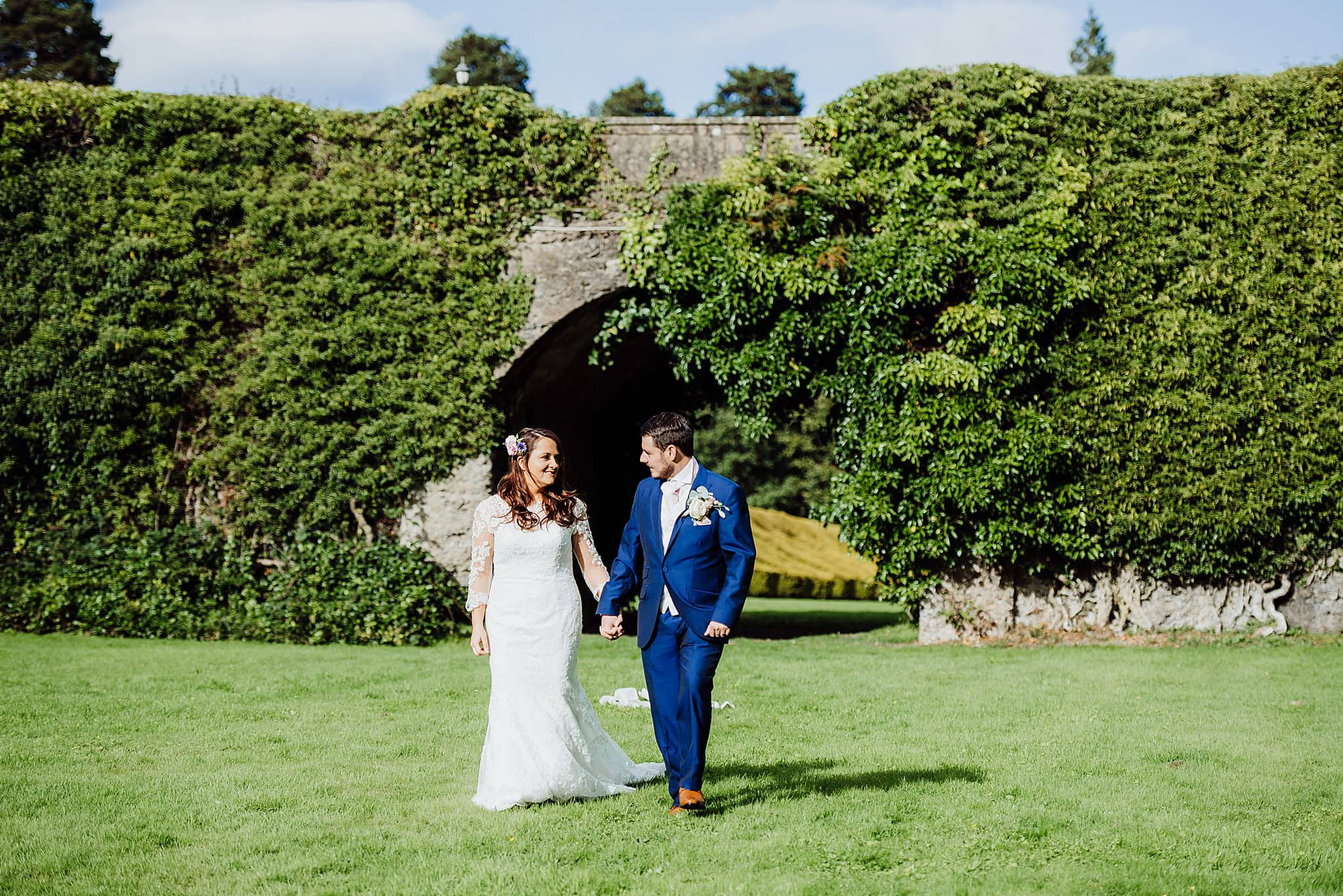 Bide and groom walk hand in hand staring at each other in the garden of Gregnog Hall wedding venue