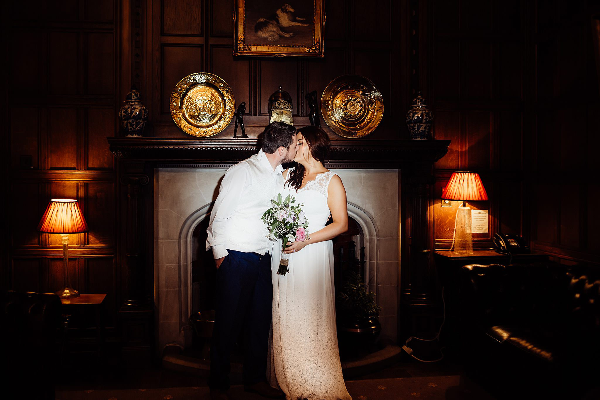 A night photo of bride and groom kissing inside Gregnog Hall infant of the fireplace with orange light eitherside