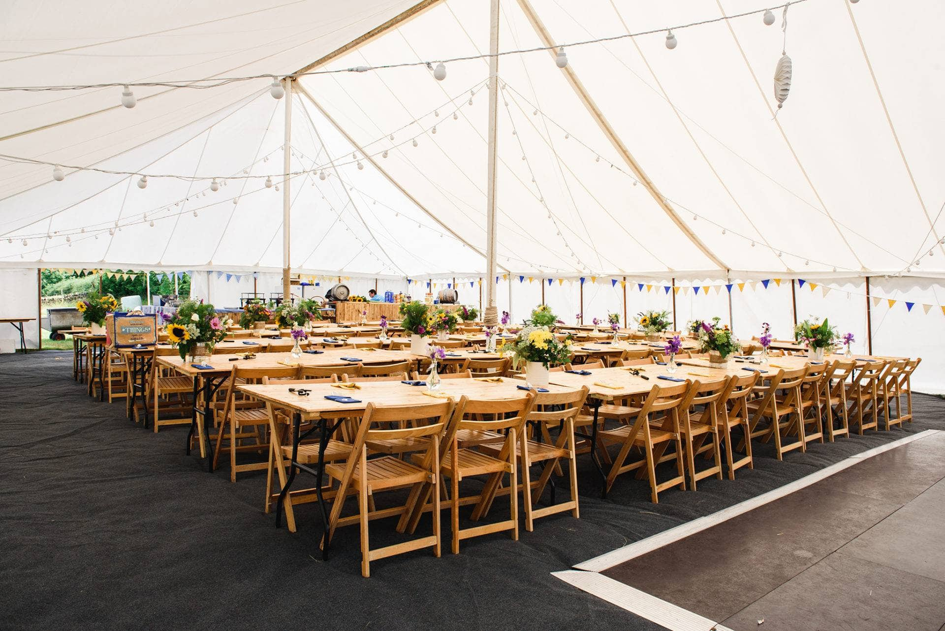 Inside of the tent with long rows of tables and chairs decorated for DIY Marquee summer wedding