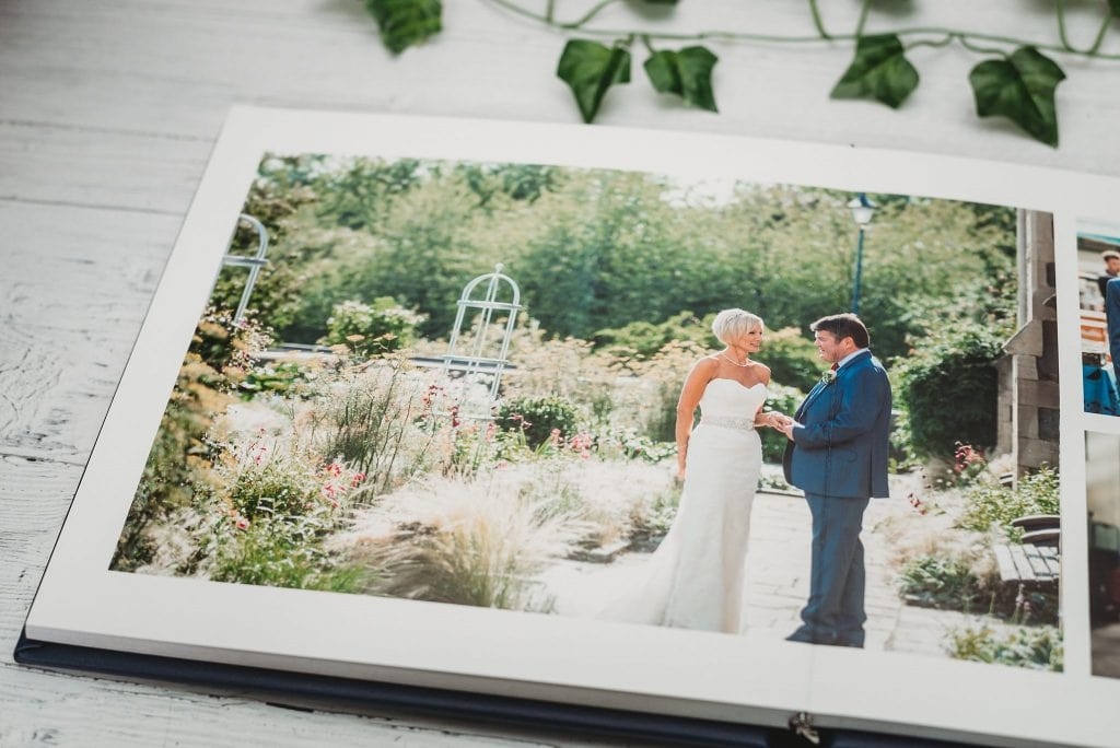 Wedding album page open showing a bride and groom holding hands in a beautiful garden