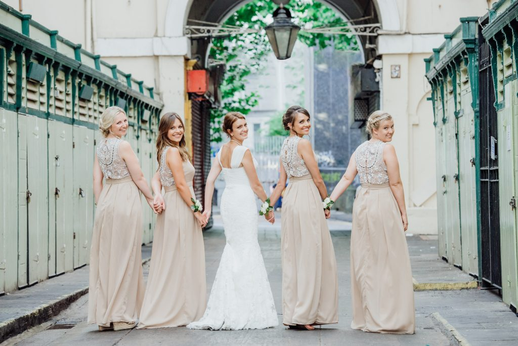 Bridesmaids holding hands walking away with their heads turned back towards the camera