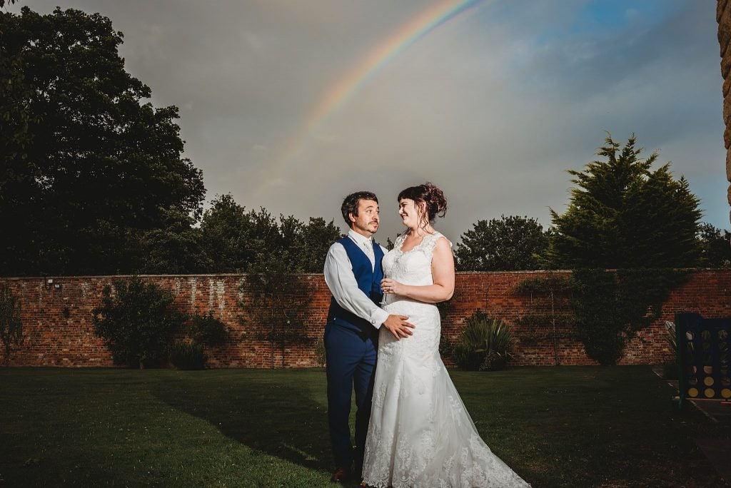 Rainbow over a bride and groom at the walled garden at Hatherley Manor