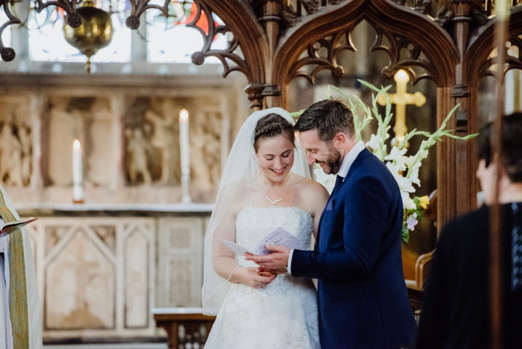 St-Andrews-church-Mells-wedding-photographer -couple sing hymns on wedding day