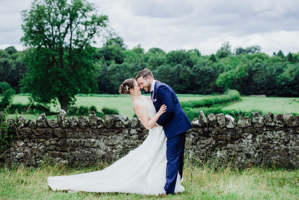 Bride being dipped backwards by groom in a field - Mells wedding photographer