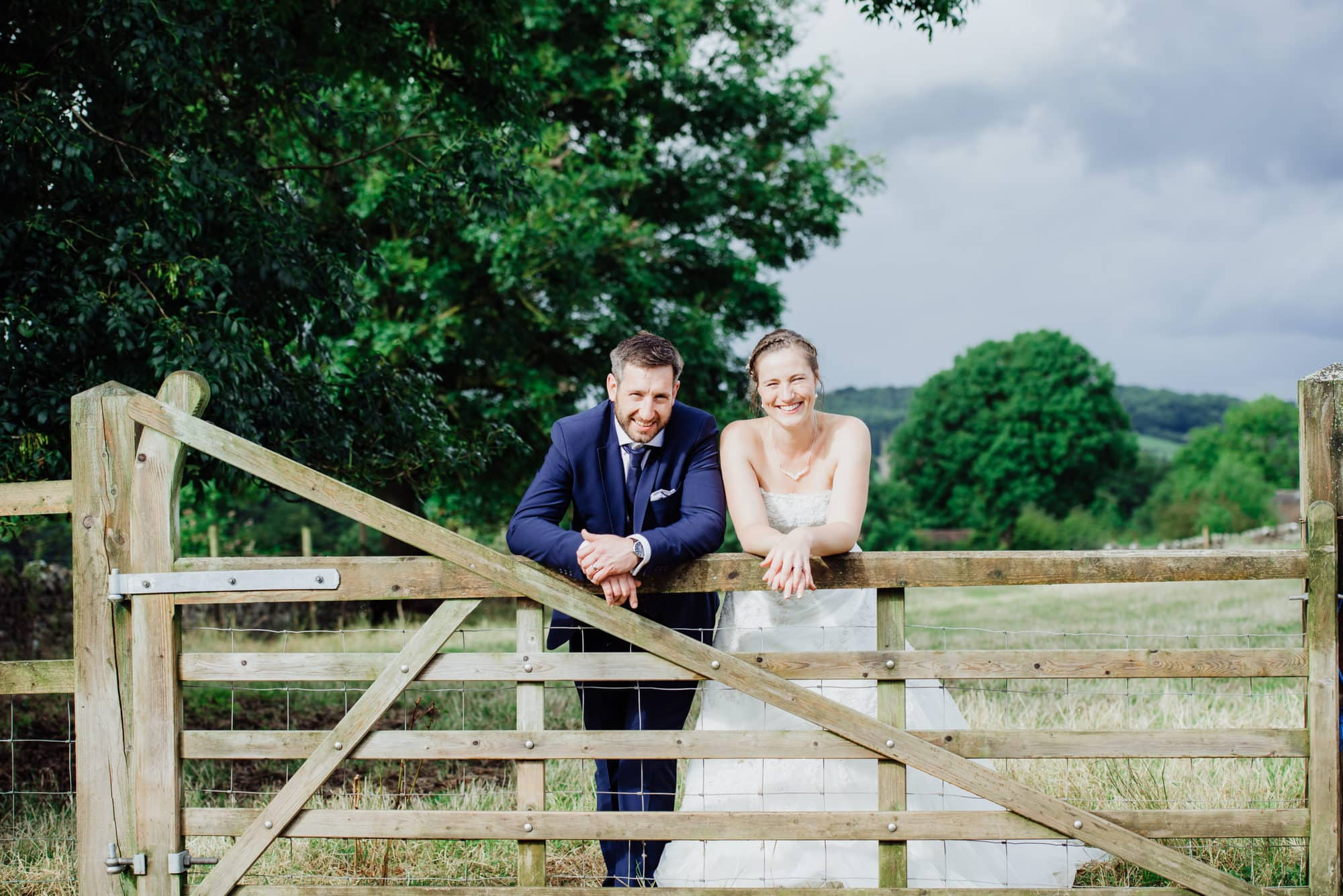 couple stood over fence in a field in Somerset