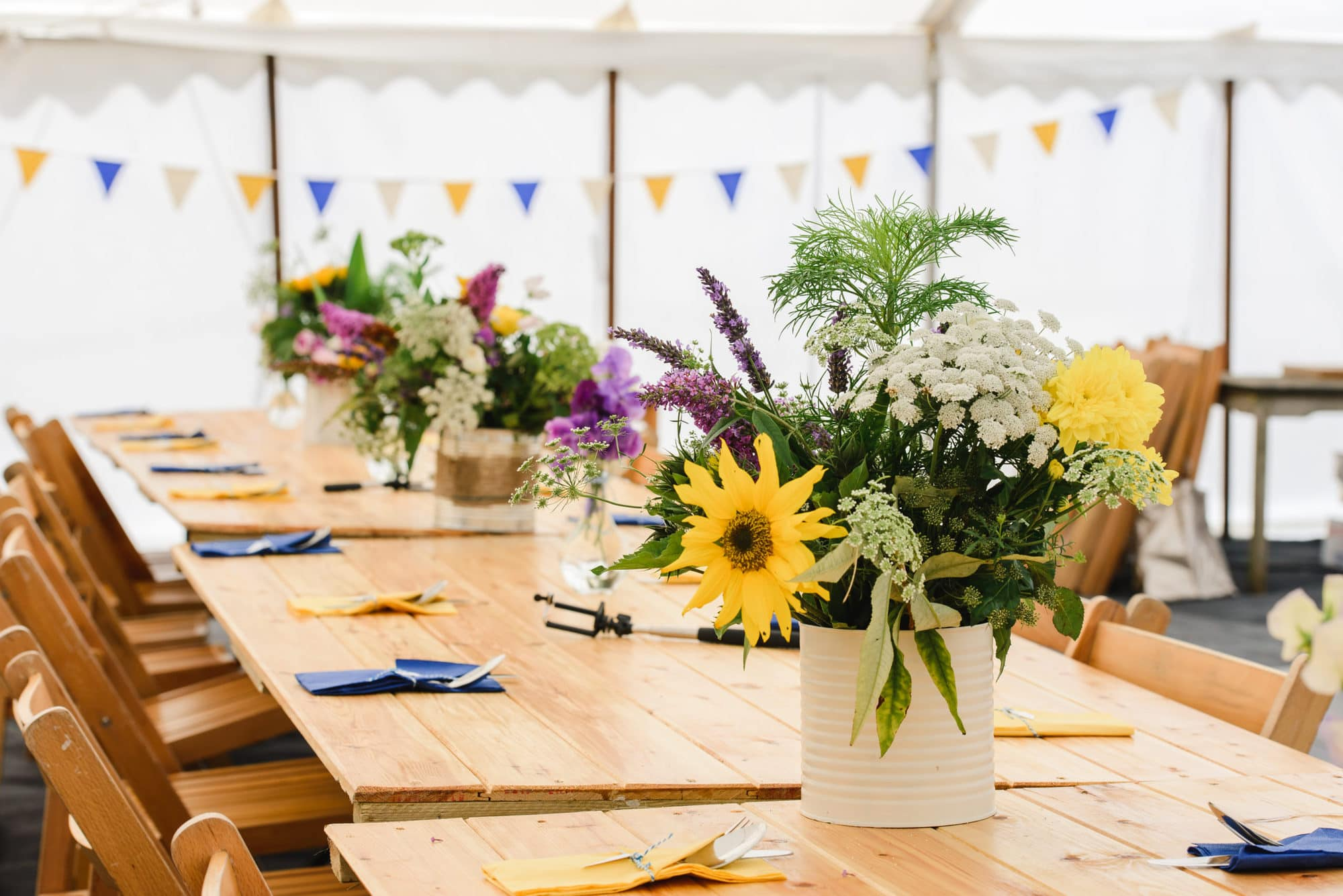 summer flowers on rustic wooden tables inside a marquee wedding