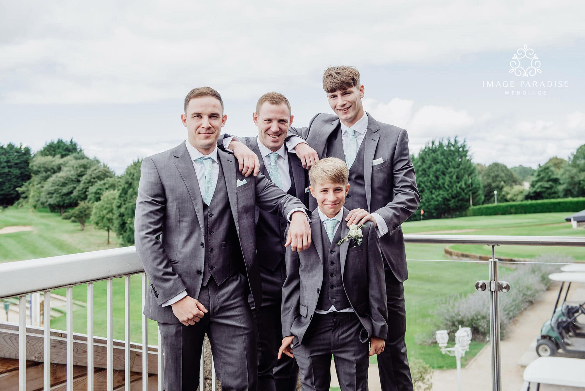 groomsmen stood on the balcony with the golf course in the backdround of the Cotswolds hotel and spa golf course wedding venue