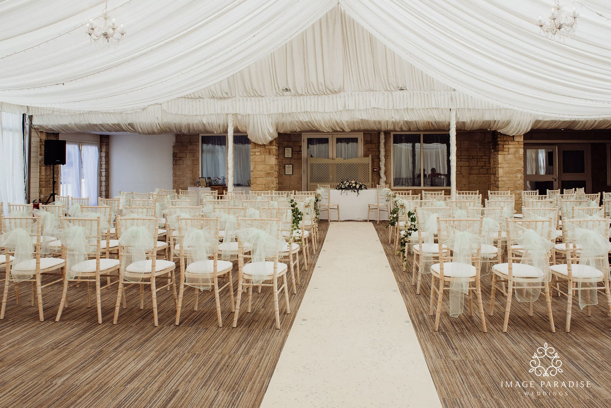View from the back of the Cotswolds hotel and spa wedding venue with chairs and cream aisle