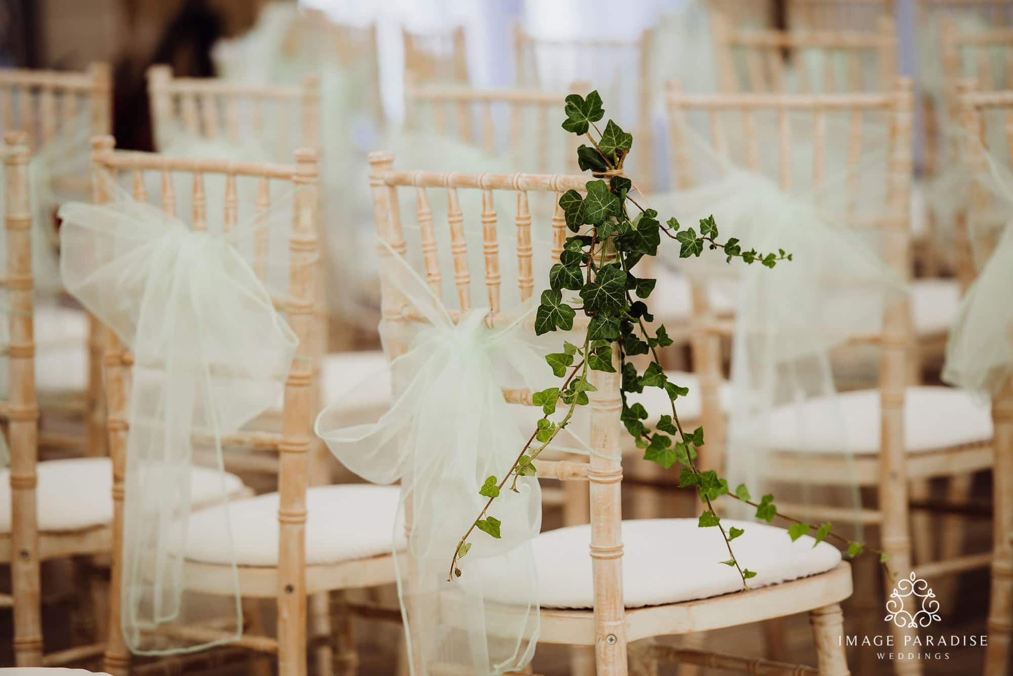 Close up view of a wedding chair with cream bow and flowers at the Cotswold hotel and spa wedding venue