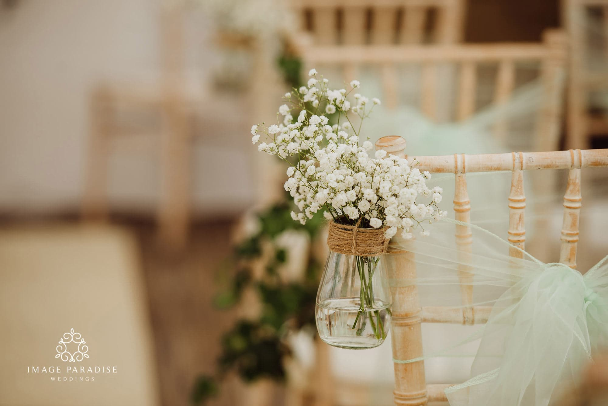 close up of flowers on the end of a chair at a wedding ceremony at Cotswolds hotel and spa wedding venue