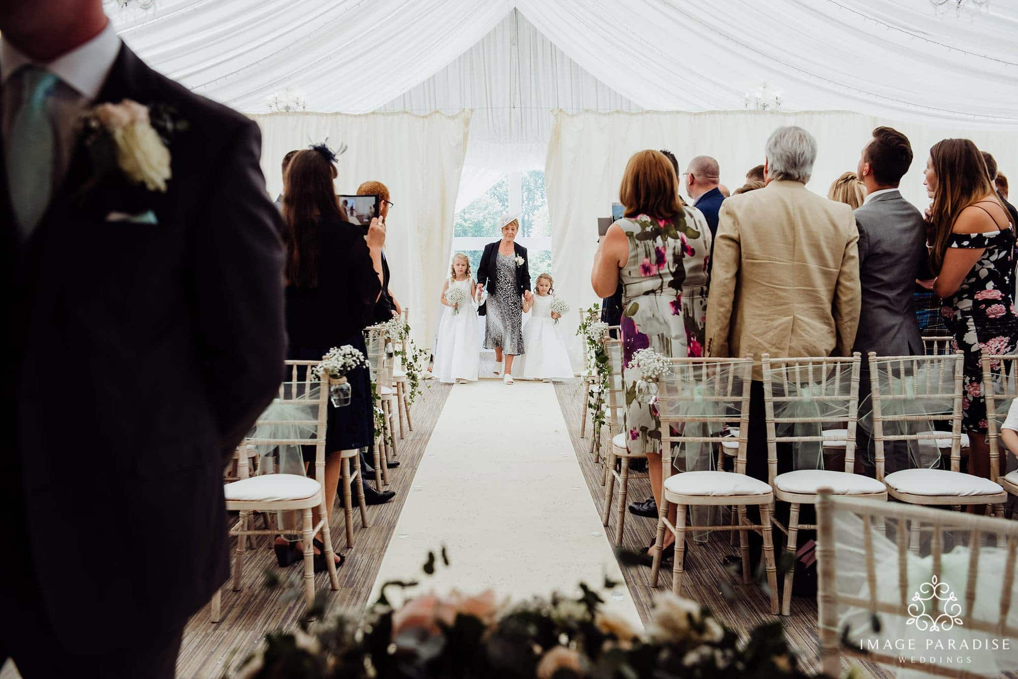 small bridesmaids walking down the aisle of the Cotswolds hotel and spa wedding ceremony