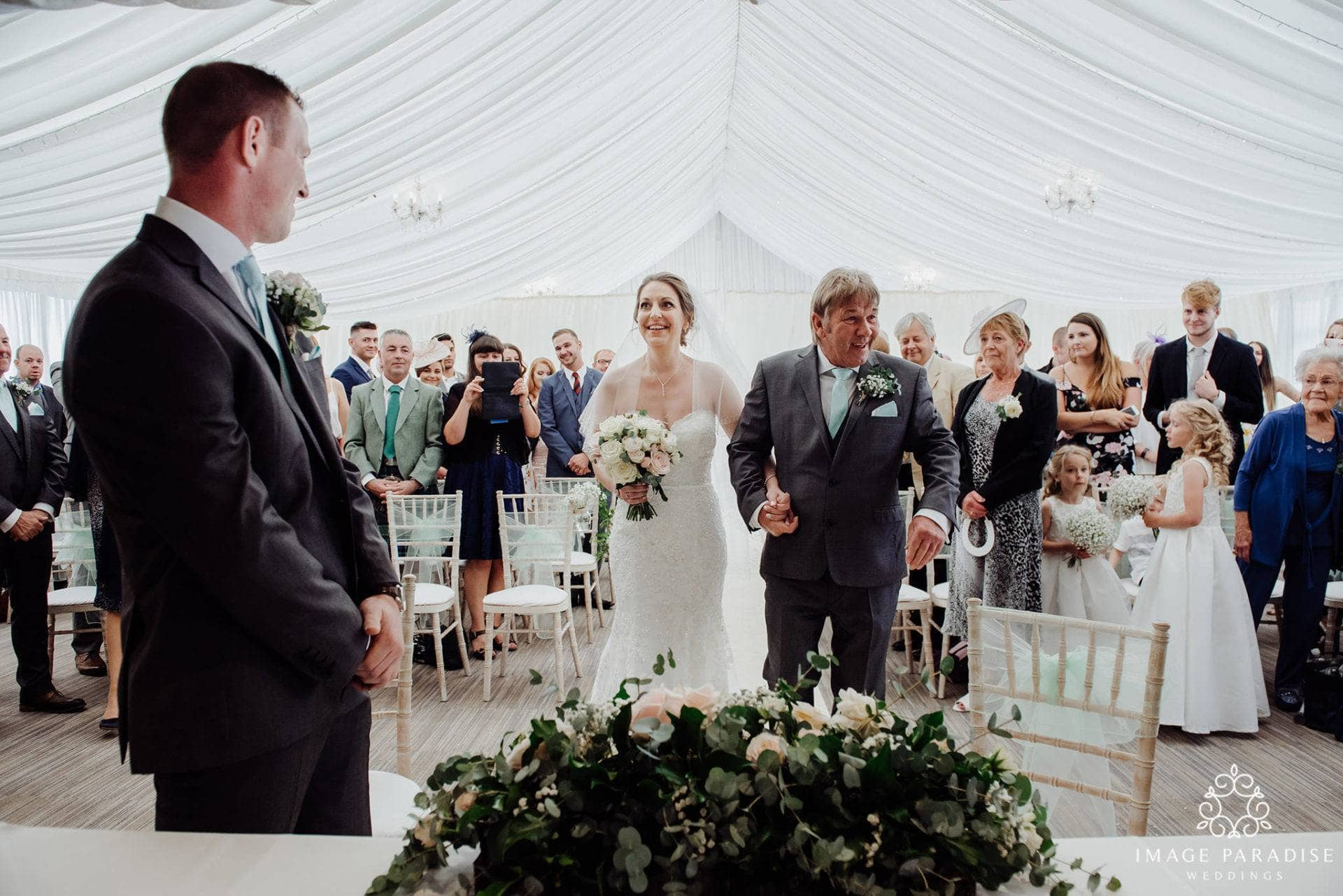bride walking down the aisle of her Cotswolds hotel and spa wedding ceremony photography