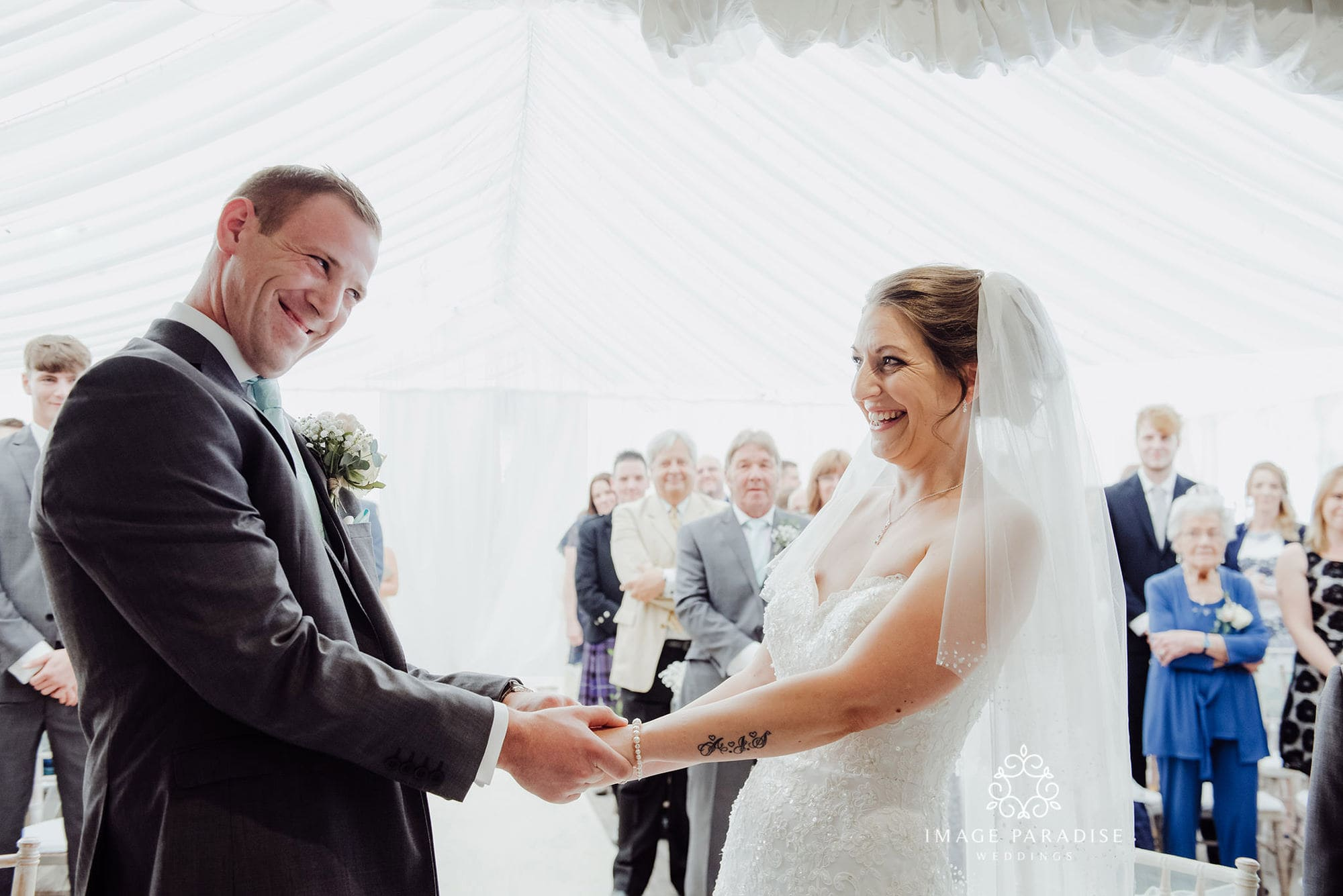wedding ceremony at the Cotswolds hotel and spa where bride and groom smile and hold hands