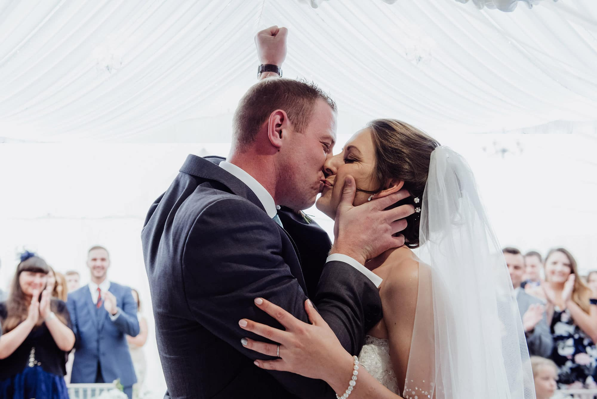 Wedding kiss with groom punching the air at the Cotswolds hotel wedding ceremony