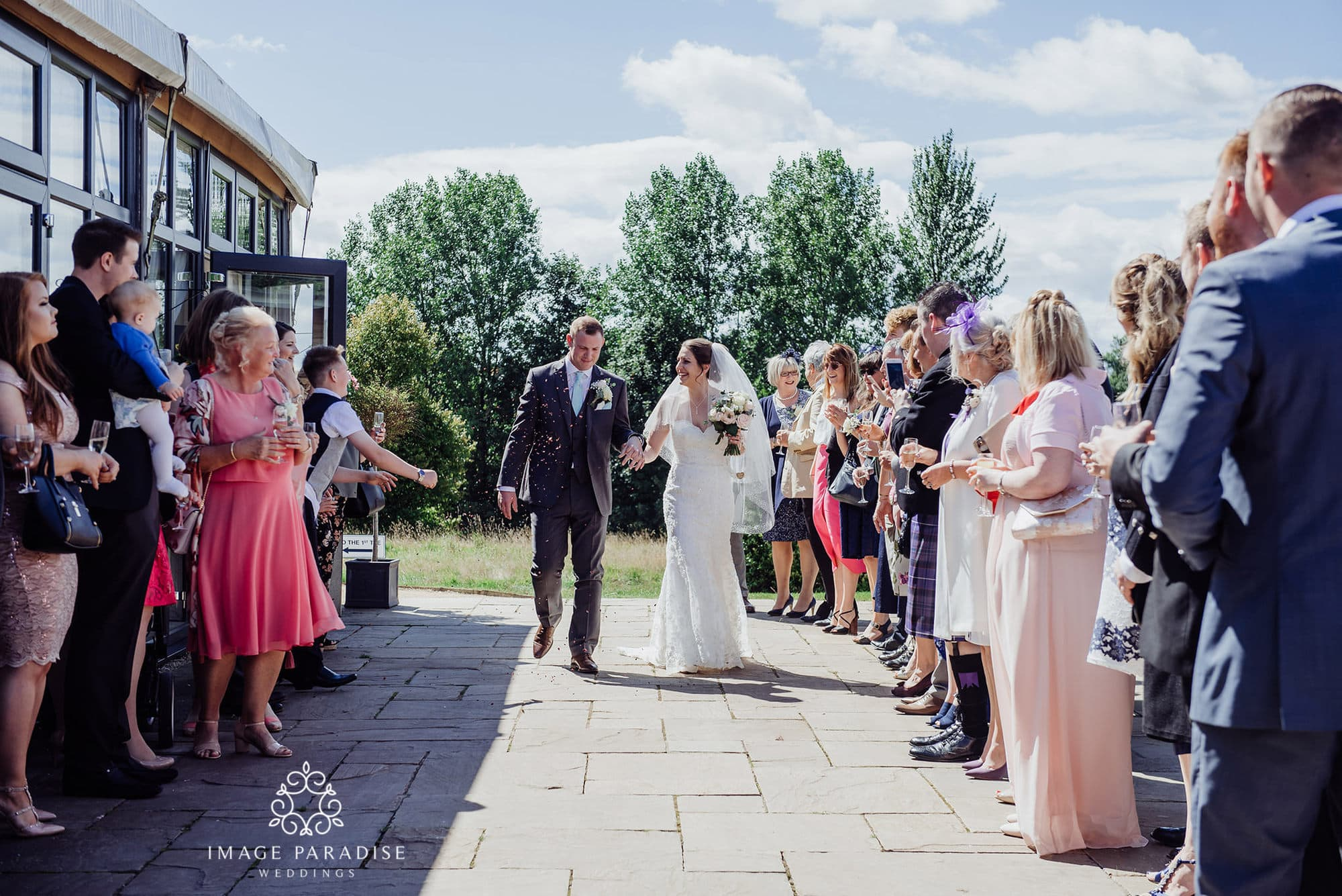 confetti being thrown by guests in the garden of Cotswolds hotel and spa