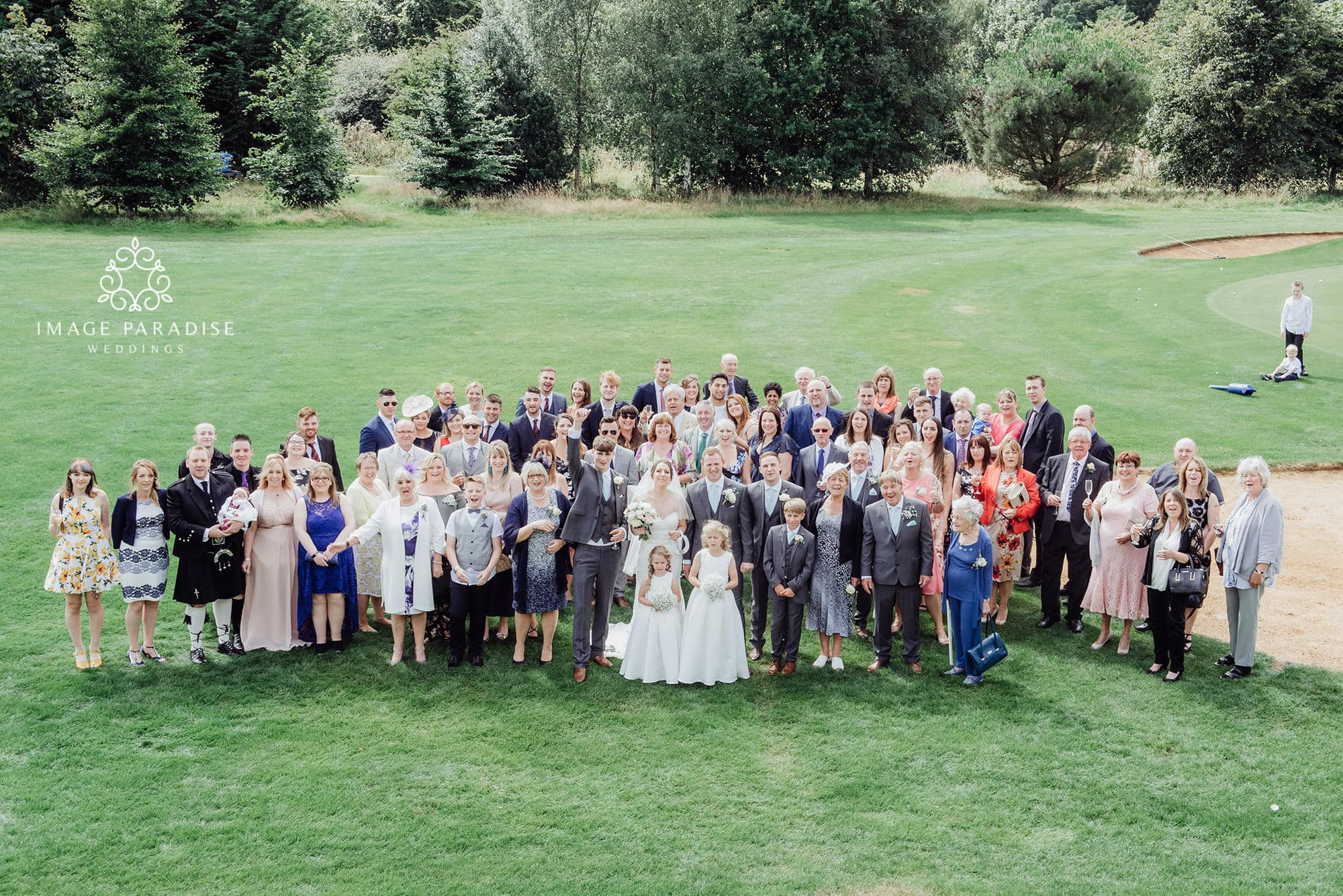 Group wedding photo on the green of Cotswolds hotel and spa