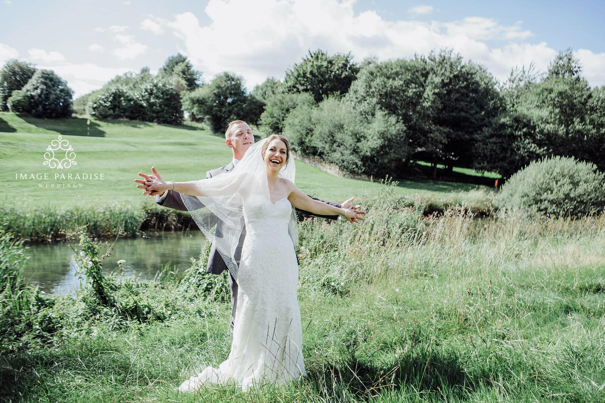 wedding photography of bride and groom posing in front of the lake on the golf course of the Cotswolds hotel and spa