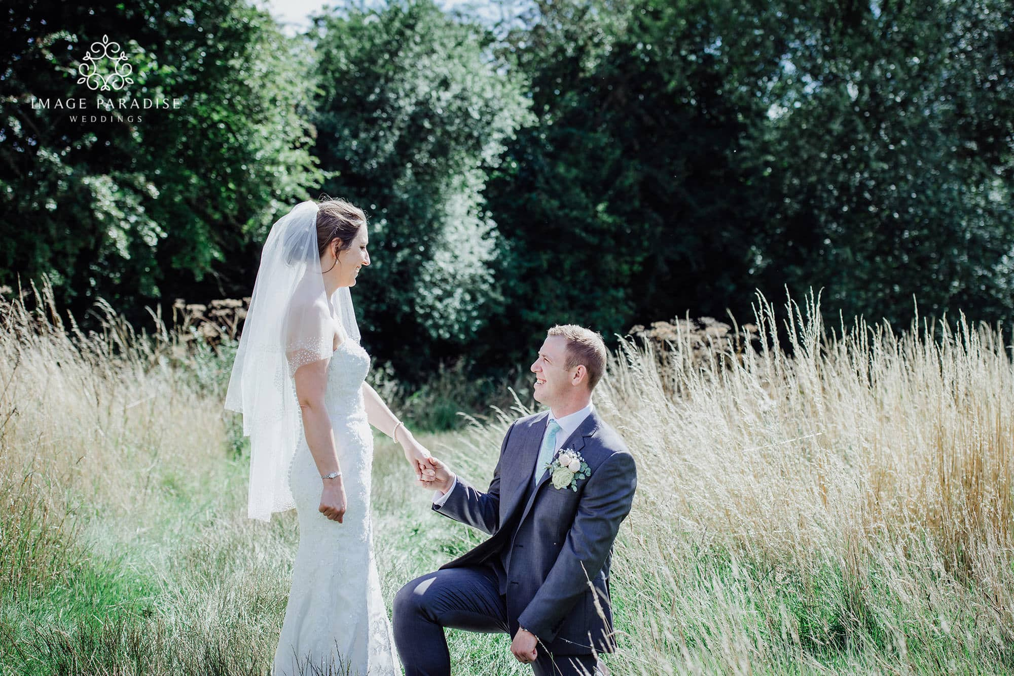 groom gets down on one knee in the grounds of the Cotswolds hotel and spa golf course wedding photography
