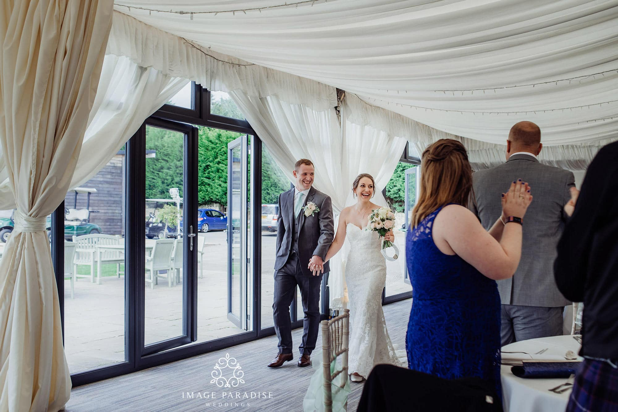 bride and groom make an entrance into the marquee at the Cotswolds hotel and spa
