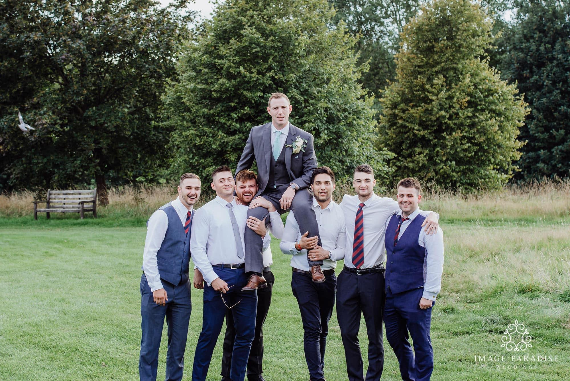 groom sits on friends shoulders