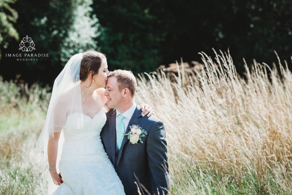 Cotswolds Hotel & Spa wedding photography bride kissing forehead of groom in the field on the golf course