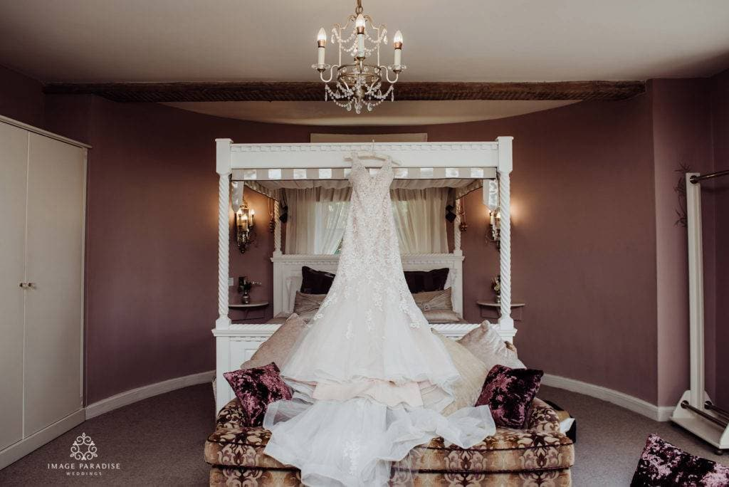 Dress hanging on the four poster bed at the bridal suite, Hatherley Manor